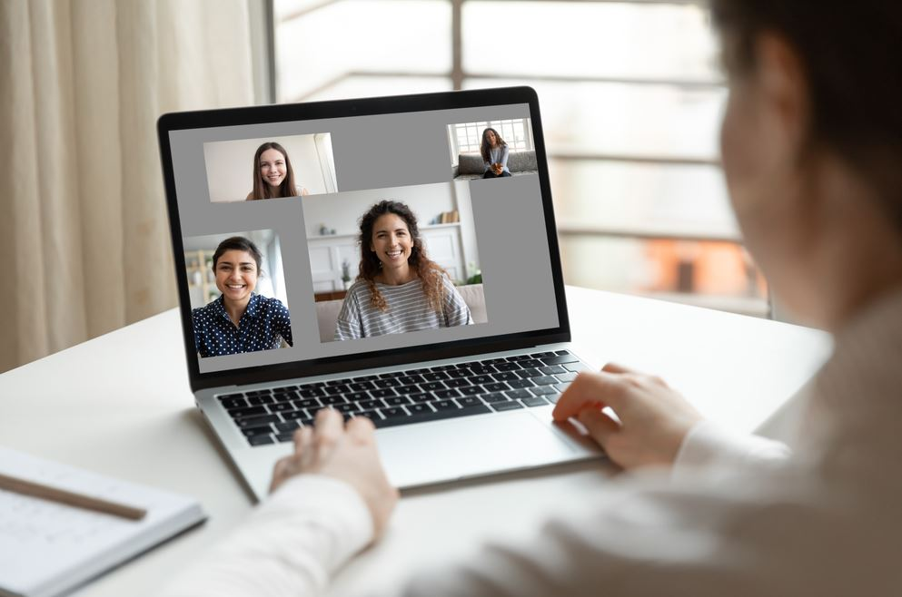 This image has an empty alt attribute; its file name is Virtual-meeting-Looking-over-shoulder-of-woman-on-laptop-talking-with-4-others-2-Shutterstock_1704143770.jpg